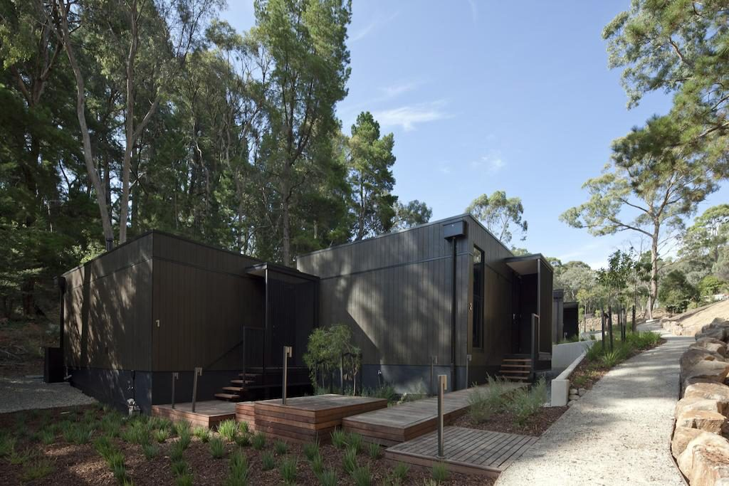Outdoor view of Villas 1 and 2 framed by the native Australian flora and lush Hepburn gardens to the rear of the villas, Geometric wooden paths lead to private Villa entrances and a path leading to guest parking is lined with neutral local standstone boulders. View from outside reception building facing easterly mid morning.
