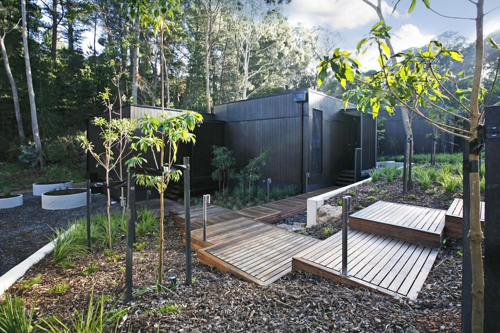 Outdoor view of Villas 5 and 56 with wooden path to front doors, surrounds by Hepburn grounds and gardens featuring classic Australian natives, facing north-easterly mid morning, Views of Lush Hepburn bush gardens towards the far grounds.