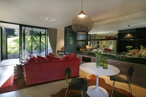 Interior of Red and Black Decor Villa, View from Kitchen dining through to lounge room and open balcony doors with outdoor view